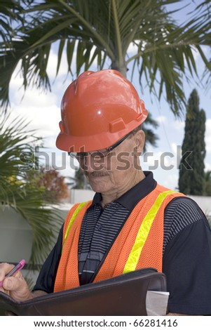Man takes notes while overlooking backyard construction.   He was in his seventies and was photographed in Bayamon, Puerto Rico in December, 2009.