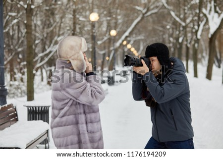 Man takes picture of woman talking phone in snowy winter park.