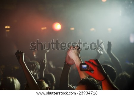 Man takes pictures on his cellphone at concert in night club.