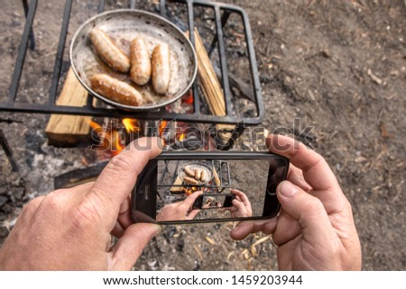 Man takes pictures on phone grilled sausages on pan grill with smoke and flame on a meadow. Barbecue picnic concept