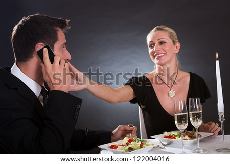 Man taking a mobile call during a romantic dinner in an elegant restaurant with the woman stretching her hand across the table as though to take it away from him