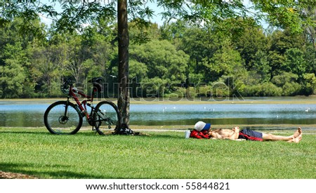 Man taking a nap at the park after riding his bicycle - Shutterstock ID 55844821