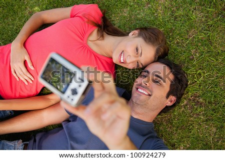 Man taking a photo of him with his friend while lying side by side on the grass