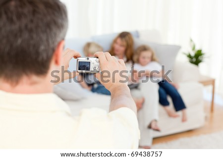 Man taking a photo of his family at home