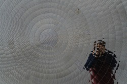 Man taking a photo of his reflection in a circular mirror installation