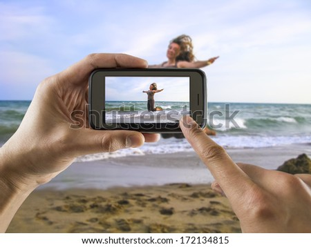 man taking a picture with your mobile phone a one woman jumping for joy on the beach