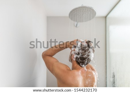 Man taking a shower washing hair under water falling from rain showerhead in luxury walk-in bath. Showering young person at home lifestyle. Body care morning routine in sunlight.
