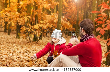 Man taking autumn outdoor picture with mobile phone. Father photograph his girl child playing in the park.