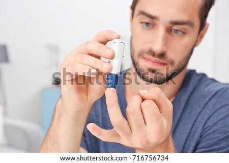 Man taking blood sample with lancet pen indoors. Diabetes concept