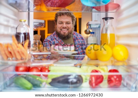 Man taking cheesecake from fridge. Picture taken form inside of fridge.