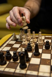 Man taking his next step on chess game. Human hand moving wooden white chess king piece on Chess board. Chess pieces in style of minimalist abstract design
