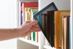 Man taking modern ebook reader from a bookshelf.