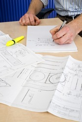 Man, taking notes on a note block with several mould technical drawings in front of him. An Industrial Design Engineer at work
