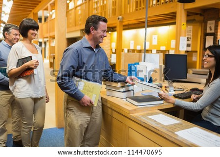 Man taking out a book at library desk - stock photo