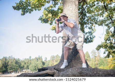 Man taking photo. Man wearing glasses taking photo of forest while standing near big tree