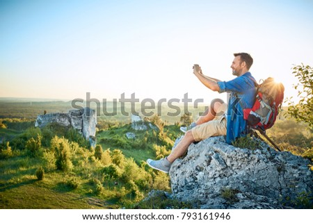 Man taking photo of beautiful view sitting on top of the rock