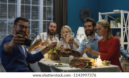 Man taking photo of diverse happy friends gathering at table on Thanksgiving day celebration and posing while having fun at home