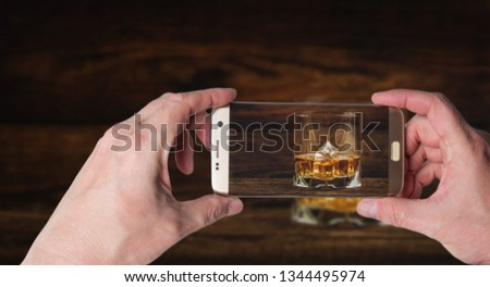 Man taking photo of Whisky or whiskey or bourbon with ice on wood background