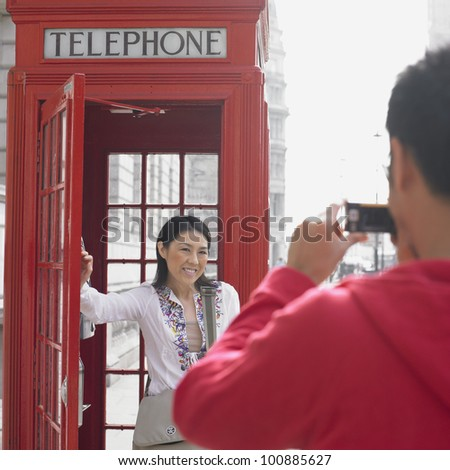 Man taking photograph of Asian woman next to public telephone box in London