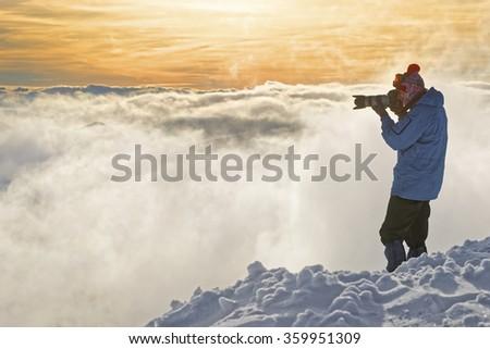 Man taking photos on top of Kasprowy Wierch in Zakopane in winter. Zakopane is a town in Poland in Tatra Mountains. Kasprowy Wierch is a mountain in Zakopane and is the most popular ski area in Poland