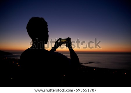 Man taking photos with phone on beach, silhouette at sunset