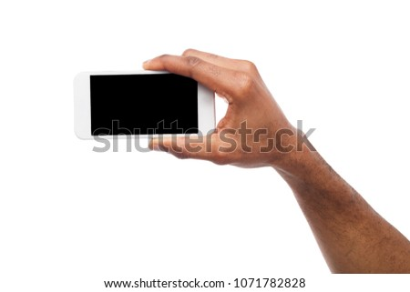 Man taking picture using smartphone. Black hand holding smartphone and shooting photo, isolated on white