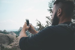 Man taking picture with phone camera of landscape