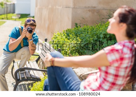 Man taking pictures of woman sitting on bench in park