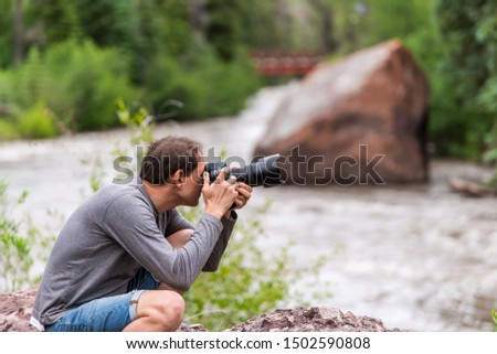 Man taking pictures with camera in Redstone, Colorado during summer with large boulder and red bridge on Crystal river by trees