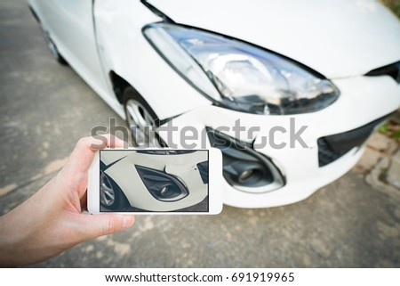 Man taking snap shot evidence photo of damaged modern white car using smartphone, insurance or road accident concept.