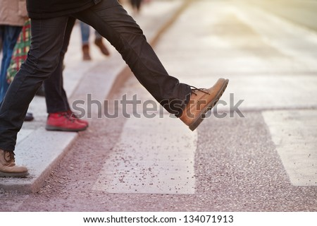 Man taking the step (onto zebra crossing)