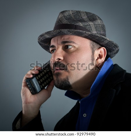 Man talking at the phone against grey background.