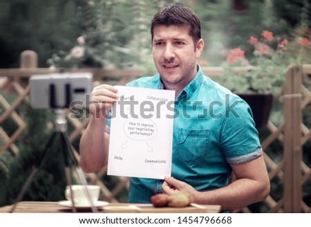 Man talking in front of a camera, holding document on How to Improve Negotiating Performance. Remote tuition on negotiation. Serious Caucasian man blogger talking to camera shooting educational video