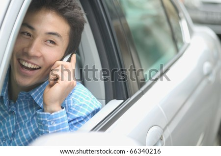 Man talking on cell phone in car