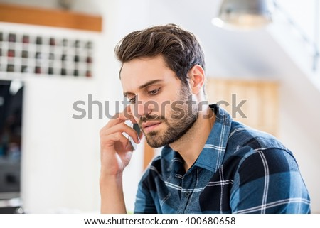 Man talking on mobile phone at home