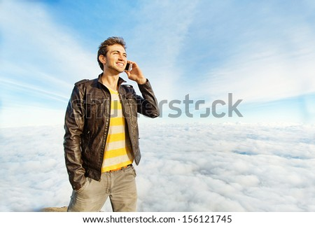 man talking on mobile phone beyond the clouds