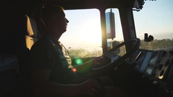Man talking on mobile phone while driving a truck. Caucasian guy is riding through the countryside on the sunset background. Lorry driver profile. Side view Slow motion Close up
