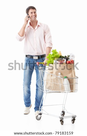 Man talking on the phone keeps a cart with food on a white background