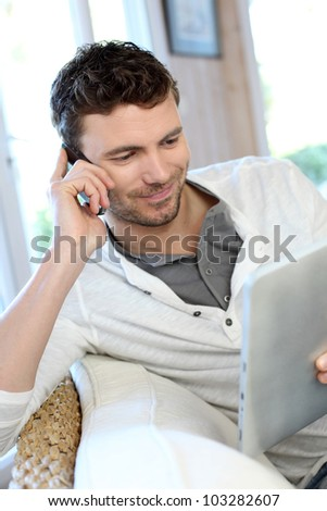 Man talking on the phone while using tablet