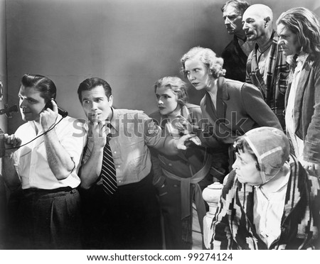 Man talking on the telephone and his friends looking at him and trying to listen Zdjęcia stock ©