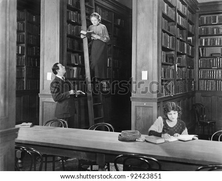 Man talking to a woman standing on a ladder in a library