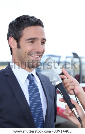 Man talking to reporters