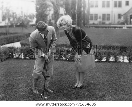 Man talking to woman while golfing