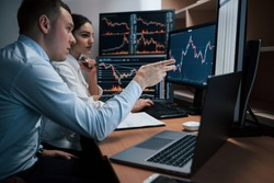 Man talks and shows on the numbers on monitor with hand. Team of stockbrokers are having a conversation in a office with multiple display screens.