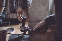Man tamping fresh morning coffee
