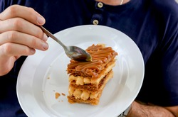 Man tastes a delicious dessert called a thousand leaves with arequipe or dulce de leche on a white plate.