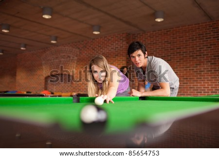 Man teaching pool to his girlfriend with the camera focus on the models