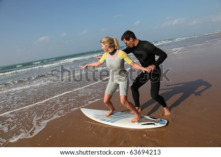 Man teaching young woman to surf