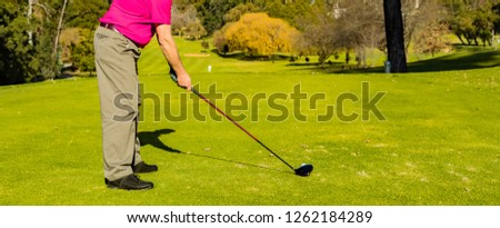 Man teeing off on a golf course Tee with a driver club