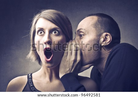 Man telling an astonished woman some secrets